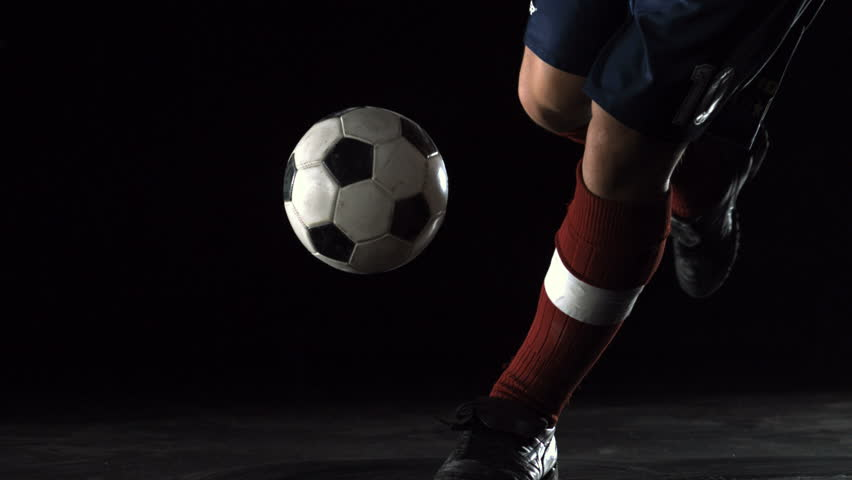 Close-up foot kicking soccer ball, Slow Motion