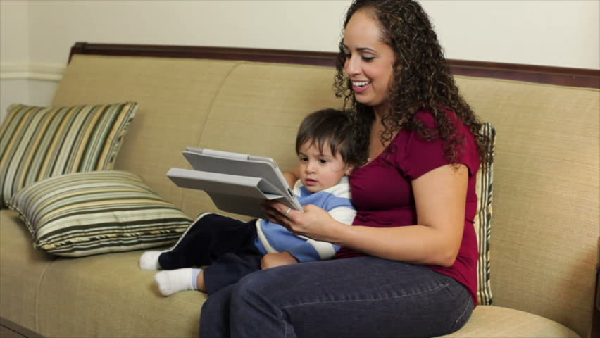A cute little toddler is enchanted by what he sees on the electronic tablet his pretty Hispanic mother is holding. - HD stock video clip