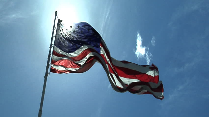 HD clip of the American flag against a beautiful blue sky. - HD stock footage clip
