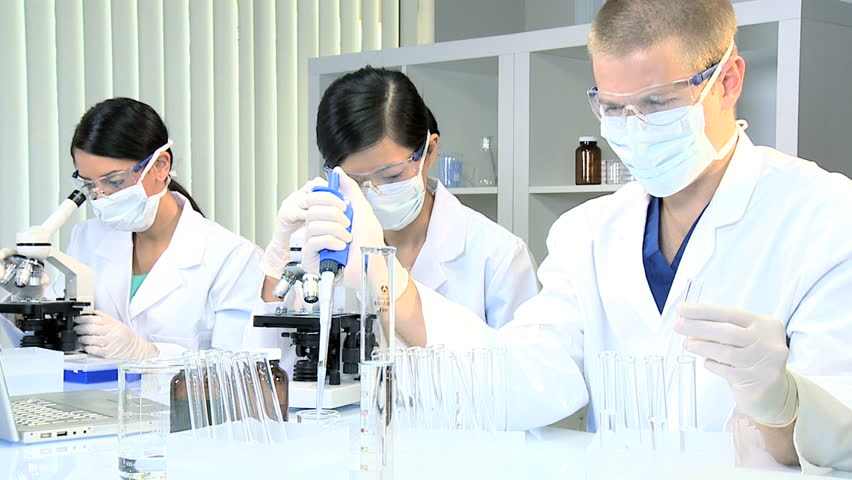 Three multi ethnic male and female medical researchers working with laboratory equipment - HD stock footage clip