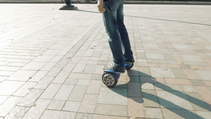 Man is riding hoverboard or electric self balancing gyro scooter board on the side walk. Modern and trendy urban transportation gadget. Popular city futuristic device among young people. | Shutterstock HD Video #19111315