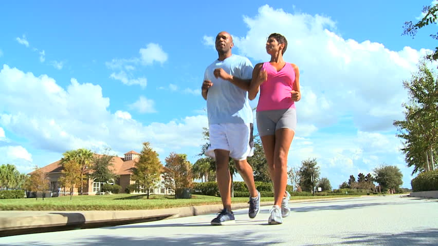 Attractive young african american couple out jogging on home roads - HD stock video clip
