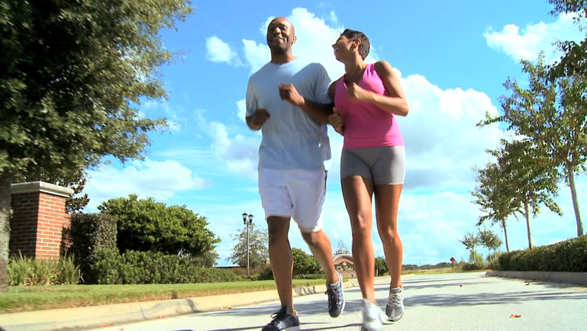 Attractive african american couple jogging on suburban roads to keep fit - HD stock video clip