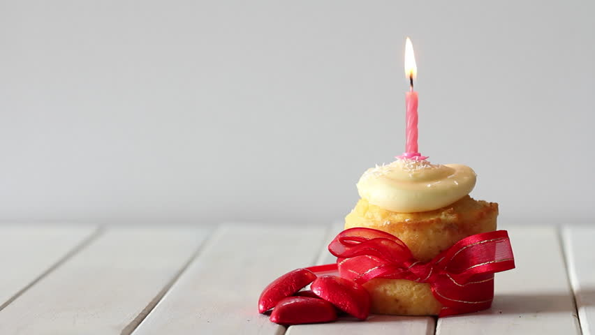 Vanilla Cupcake with Red Ribbon, Red Chocolate Hearts and Burning Candle Getting Blown Out #19217128
