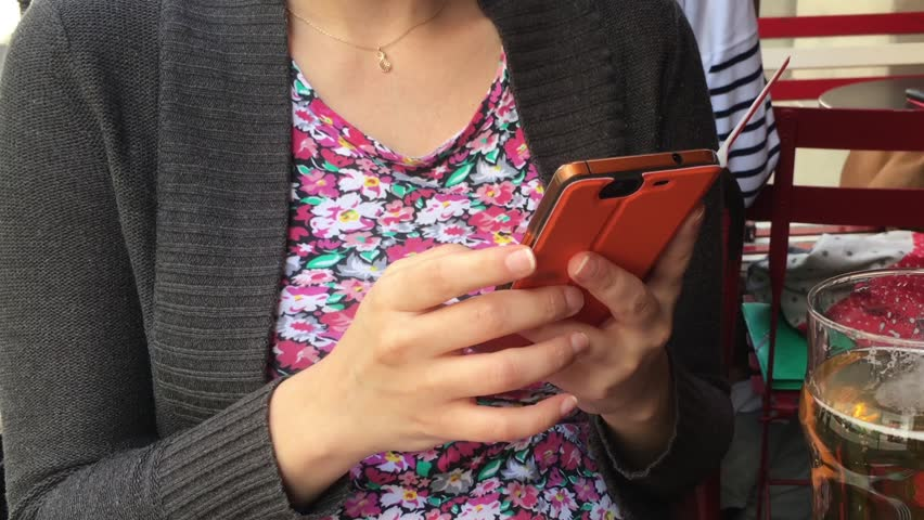 Girl Text Message On Smart Phone In a Bar, Zoom Out. Girl sitting in a bar sending messages on a smart phone and having a beer.   Shutterstock HD Video #19224121