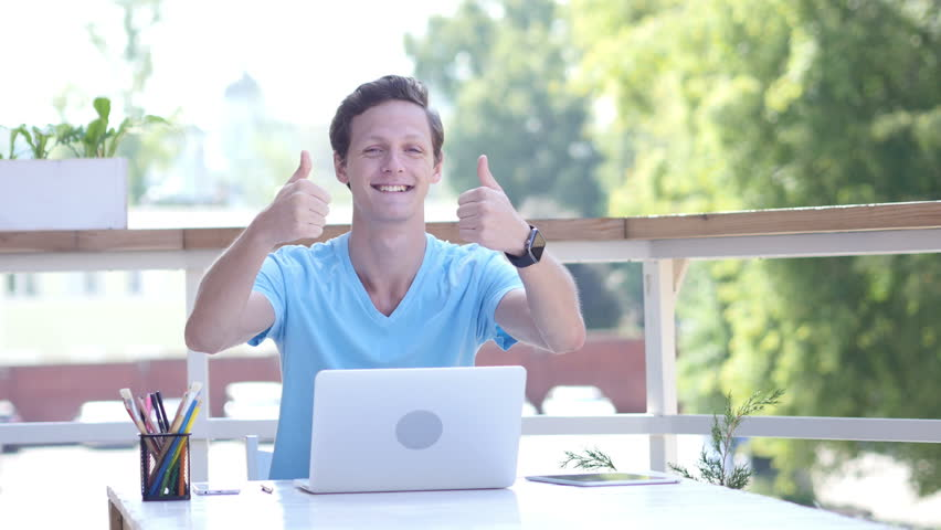 Thumbs Up by Young Man at Work, Sitting on Desk, Outdoor | Shutterstock HD Video #19227460