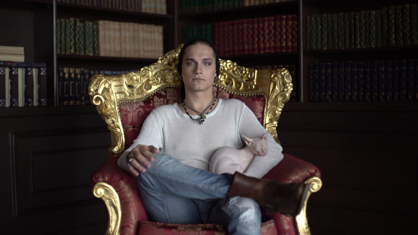Strange man sitting on a throne in the library and holds Sphynx cat
