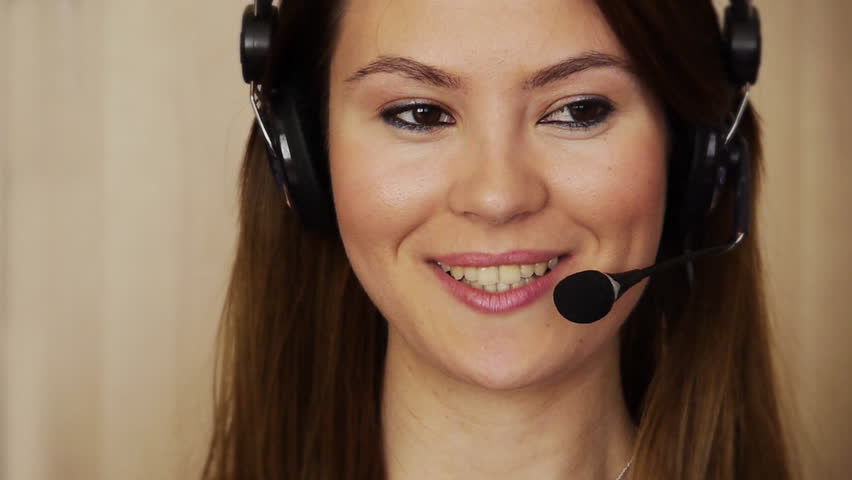 Young woman at call using headphones with microphone, talking - Direct Shot - Looking Around - HD stock footage clip