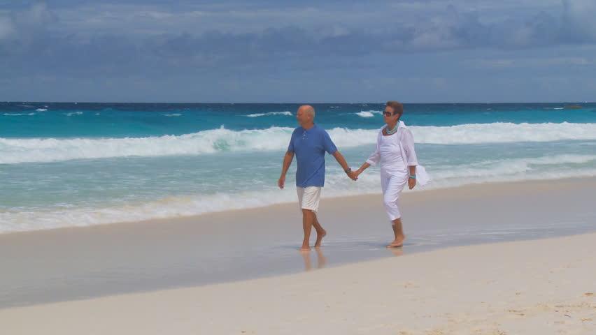 camera following senior couple walking on the beach