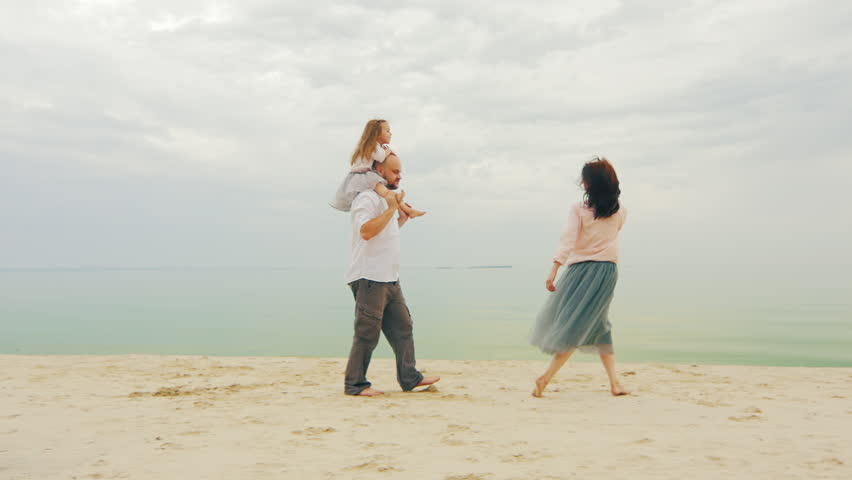 Happy family of three people walking along the sea. Against the background of the beautiful sky | Shutterstock HD Video #19363639