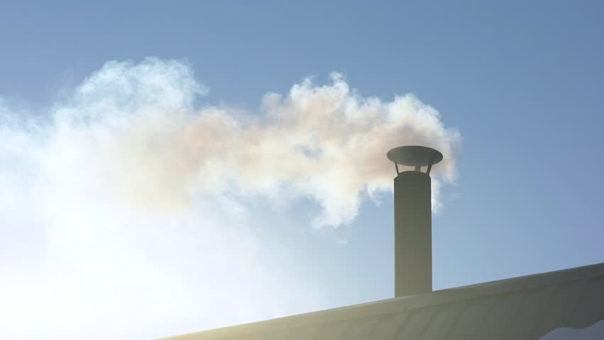 Smoke comes from the chimney of the house. The pipe on the roof. Chimney. Country house. The house with a chimney. Smoke in the blue sky. Smoke stacks and sky clouds