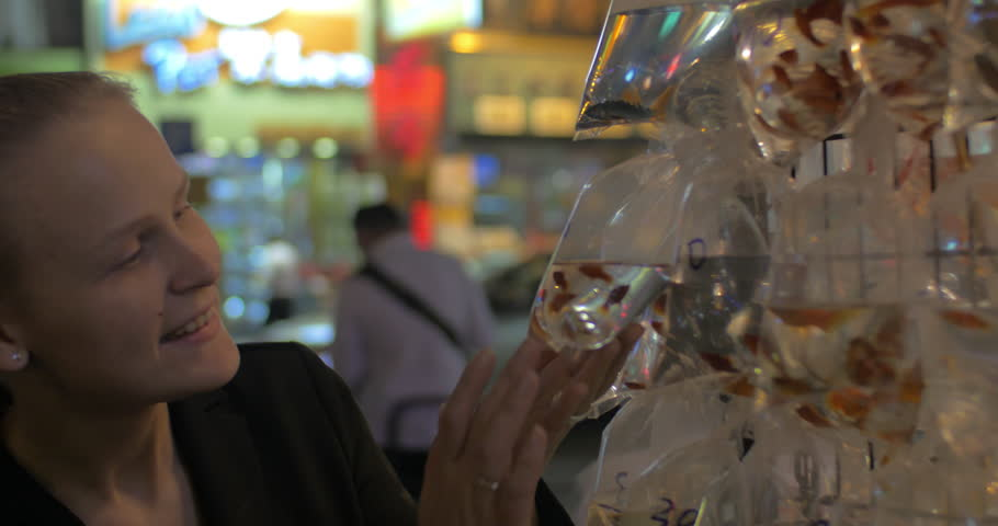 Woman looking at goldfish in plastic bags sold in street market of Hong Kong | Shutterstock HD Video #19477444