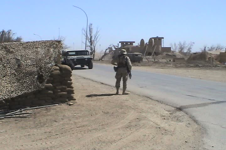 IRAQ - CIRCA MAY 2003: Checkpoint at Talil, mileage signs on post to Wrigley Field and Atlanta, soldier holding weapon in back of humvee with Baghdad Mosque in Background. - SD stock video clip