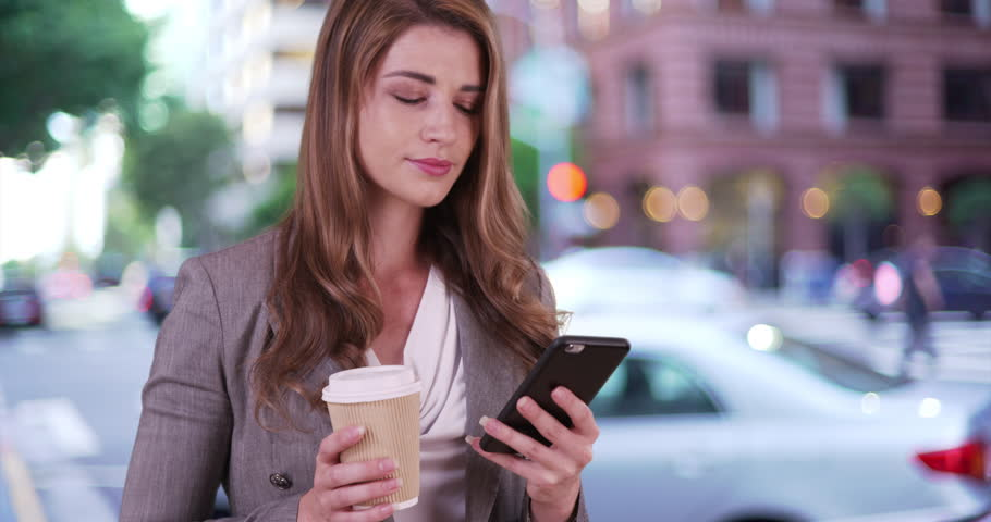Young businesswoman talking on the phone with a client. Successful and professional woman holding coffee and talking on smartphone