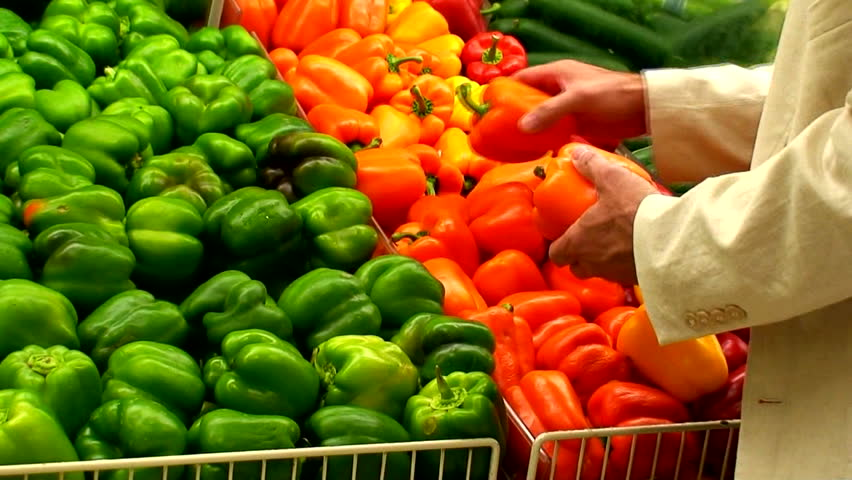 A man in the produce section looking over the colorful peppers. - HD stock video clip