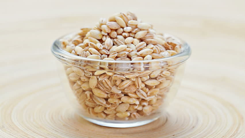 Pearl barley heap in a glass bowl rotating on wooden plate, loop ready