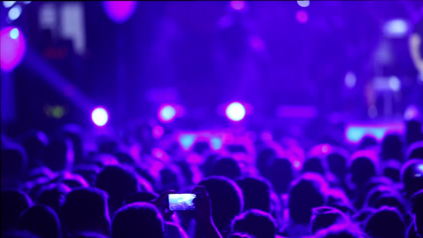 Defocus silhouettes of concert crowd in front of bright stage lights | Shutterstock HD Video #19597261