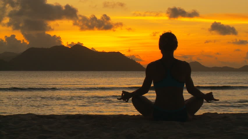 young woman in lotus seat on beach at tropical sunset