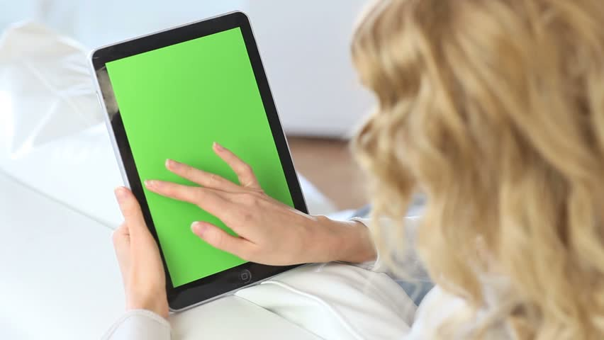Back view of woman at home using electronic tablet