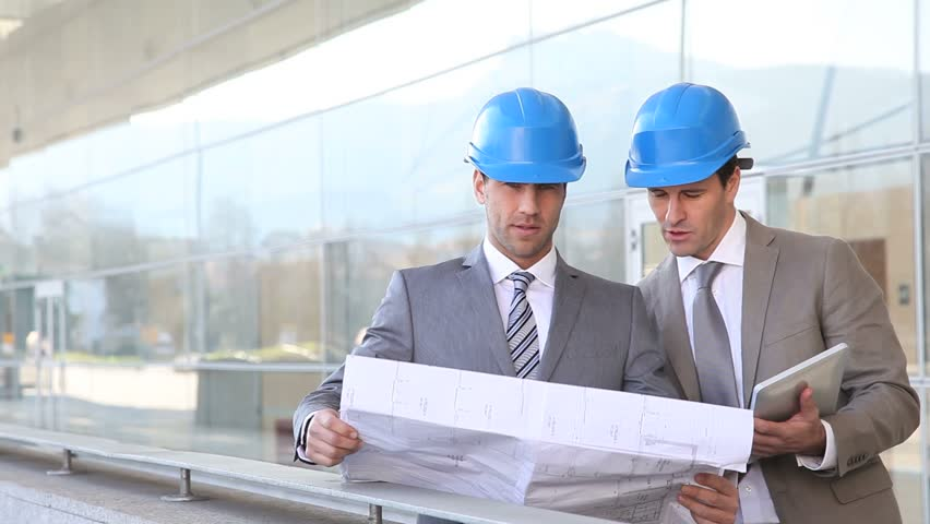 Architects checking construction site with plan outside - HD stock video clip