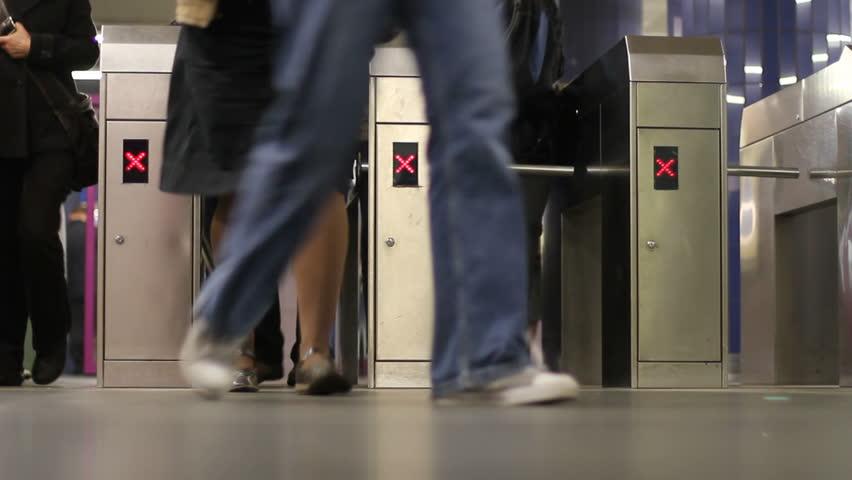 Passengers pass through subway turnstiles