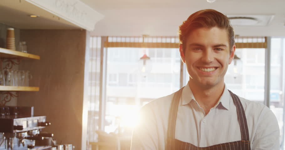 Portrait of waiter smiling at camera in cafe 4K