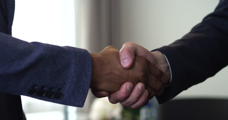 We see a handshake between two businessmen. The agreement between them had been reached. One of them is an African American/Handshake of Two Businessman - is the Completion of the Transaction   Shutterstock HD Video #19786783