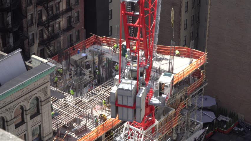 Construction workers and large crane work hard to build a new midtown Manhattan building for expensive apartment and office real estate. Union workers and operators bid on job site for contract