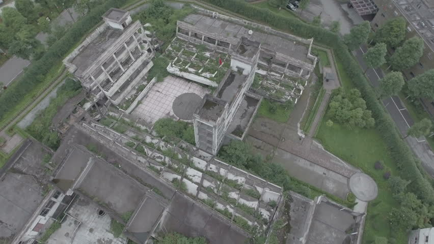 Rotating aerial shot of a partly collapsed school building, now serving as a memorial museum to the 2008 Wenchuan earthquake in China. D-log profile. | Shutterstock HD Video #19835086