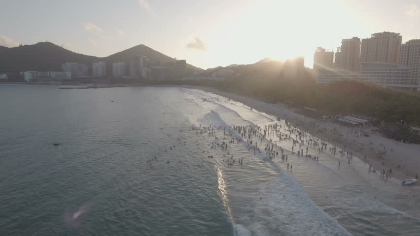 People take a swim at sunset at a busy beach on Hainan island in China. | Shutterstock HD Video #19838299