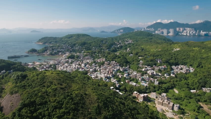 Aerial drone flight towards a small fishing village community on Lamma island, with the modern skyline of Hong Kong in the background. | Shutterstock HD Video #19843195