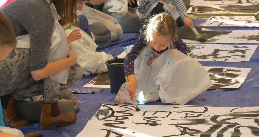 Families, Mums With Kids Paint Together at Master Class, Kids Are Painting Black, Writing on a Big Sheets of Paper. Family Master Class on Drawing and Painting in Opole, Gallery of Modern Art. People | Shutterstock HD Video #19890283