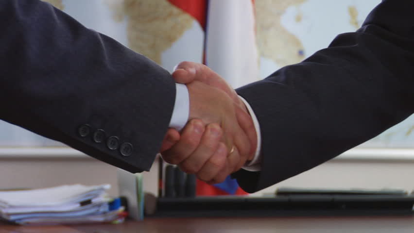 Men exchange hand shake against the Russian flag. - HD stock video clip
