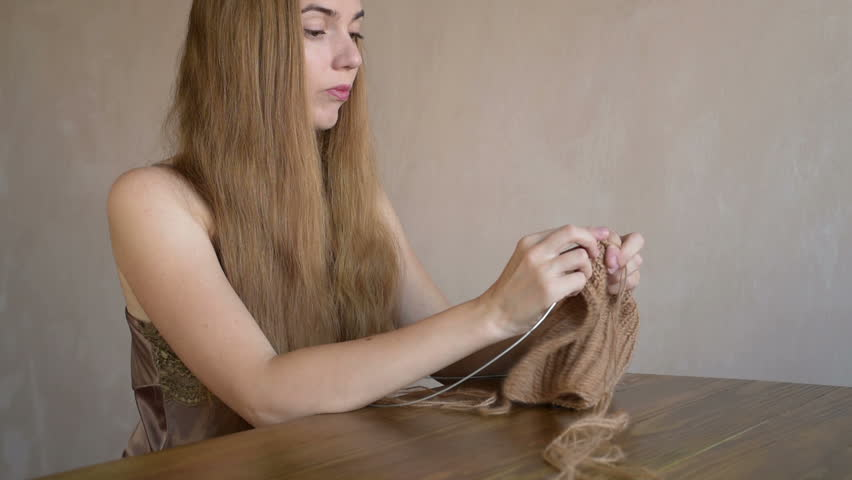 Woman with long blonde hair knitting