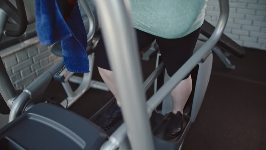 Tilt up of overweight blonde woman training on elliptical machine in the gym | Shutterstock HD Video #19917148