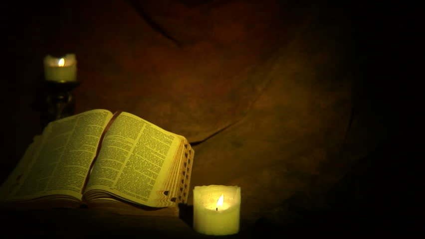 Dolly moves left to show old gothic bible with candles. Shot with DOF adapter, focus on bible