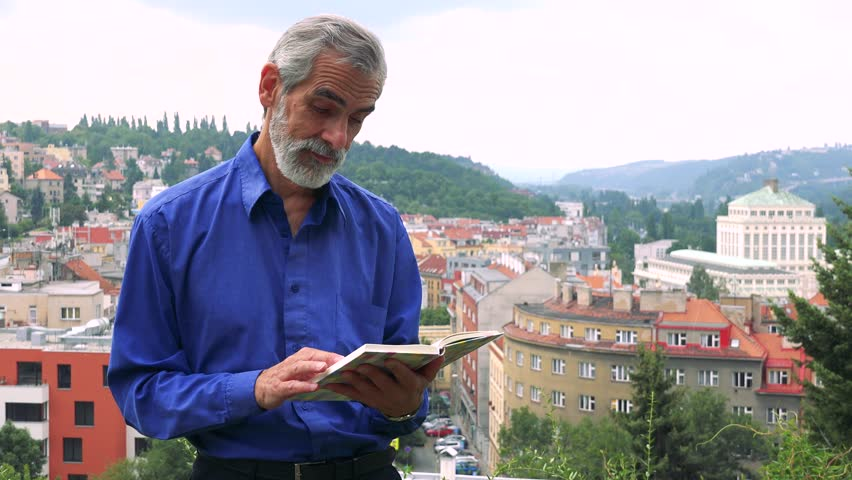 Old senior man man reads book - city (buildings) in background | Shutterstock HD Video #20076106