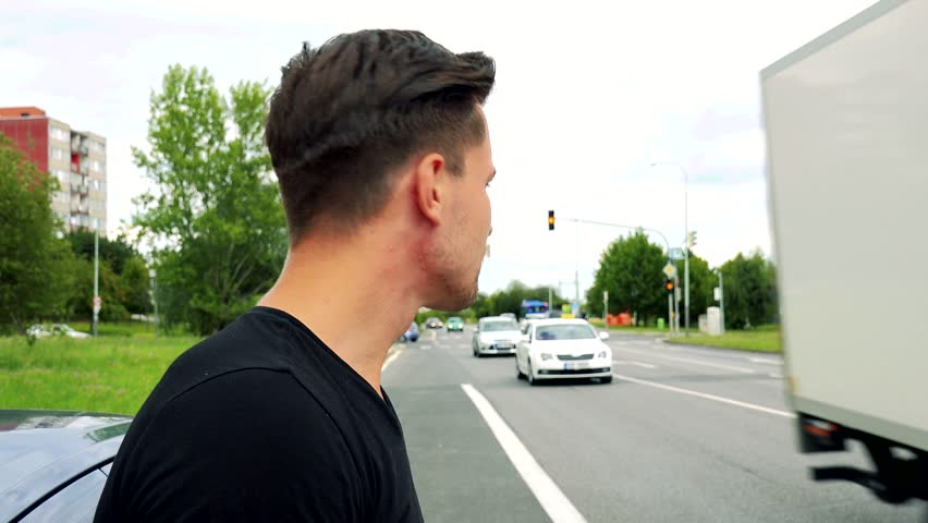 Young handsome man stands next to the car and looks around -  road with passing cars and nature | Shutterstock HD Video #20093503