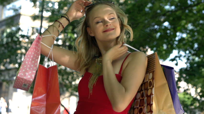 Pretty, blonde girl holding shopping bags and looking happy, slow motion shot at 240fps  | Shutterstock HD Video #20096113