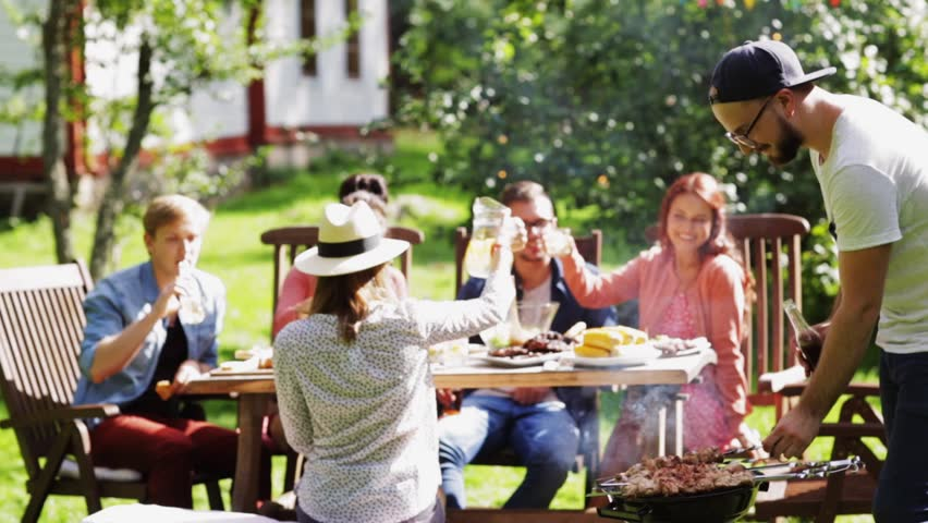 Leisure, food , eating, people and holidays concept - happy man grilling meat on barbecue party for his friends and drinking beer from bottle at summer garden | Shutterstock HD Video #20117947