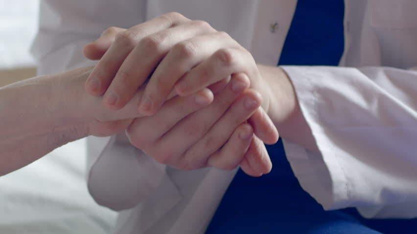 Close-up of a doctor holding a wrinkled hand at the hospital. Man wearing a white coat comforting a weak old patient. | Shutterstock HD Video #20129728