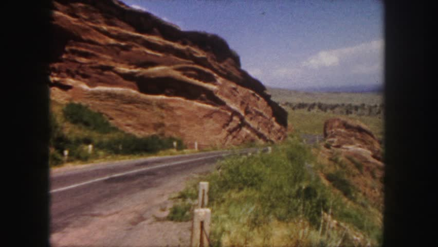 COLORADO 1958: red rocks denver area classic car driving past monoliths.
