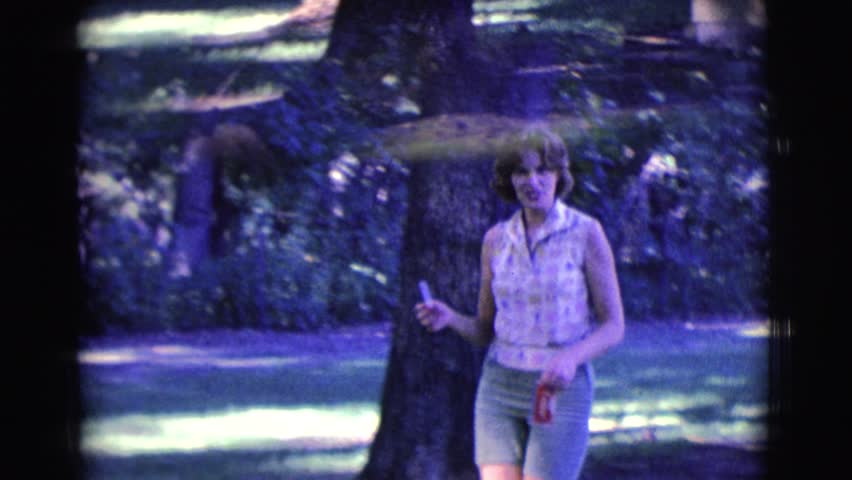 CLARKSDALE, ARIZONA 1961: woman walks through wooded area carrying cigarette to give to man. | Shutterstock HD Video #20144101
