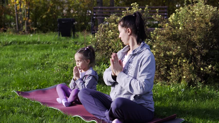 Mother and her little daughter meditating together in the park | Shutterstock HD Video #20195023