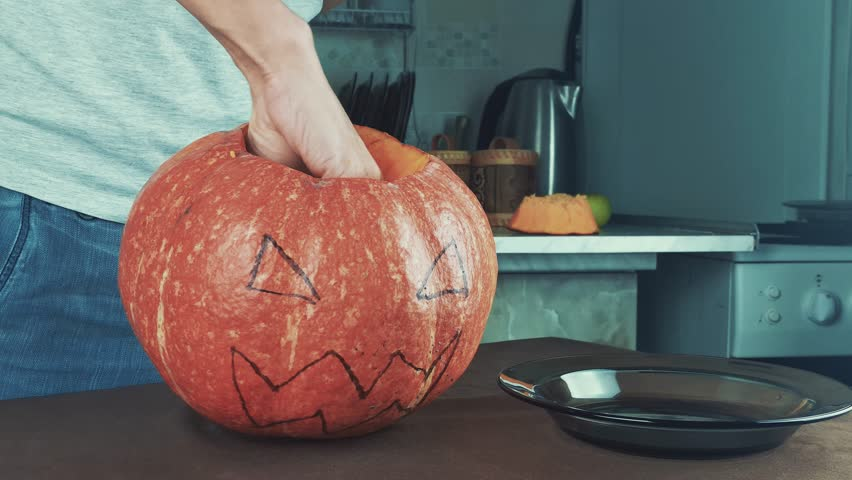 Male hands scooping out seeds and contents of pumpkin. Halloween theme, jack lantern. Medium shot 4k | Shutterstock HD Video #20200702