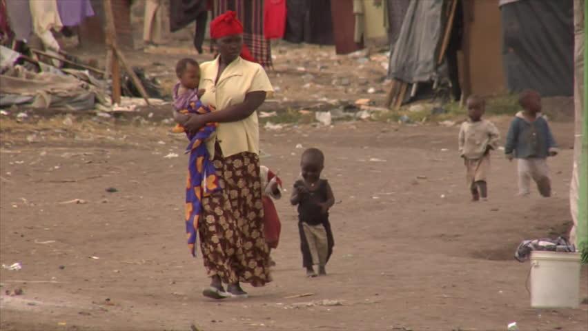 KENYA - CIRCA 2006: Unidentified African woman walks up a street followed by