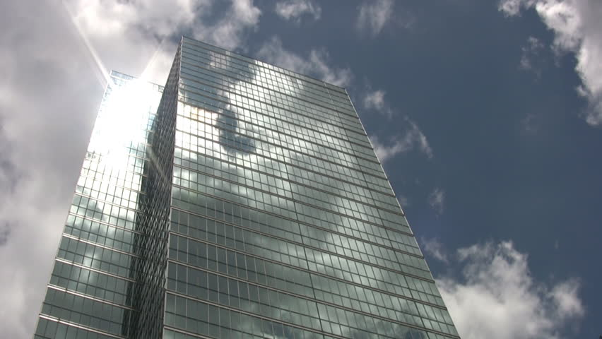 A tall mirrored skyscraper reflects the clouds going by in a timelapse shot. - HD stock video clip