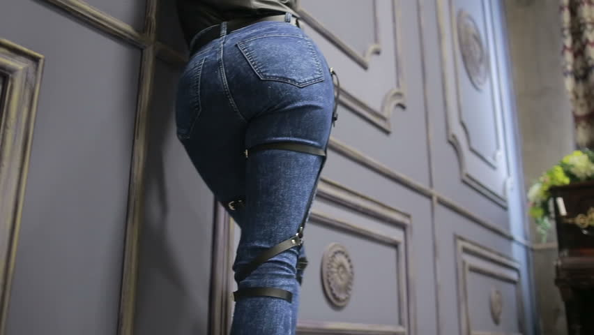 Girl in jeans with leather garter new fashion trends. straps on the hips | Shutterstock HD Video #20484733