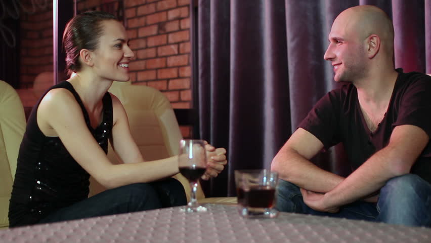 Young attractive couple looking at each other and chatting in the bar  - HD stock video clip