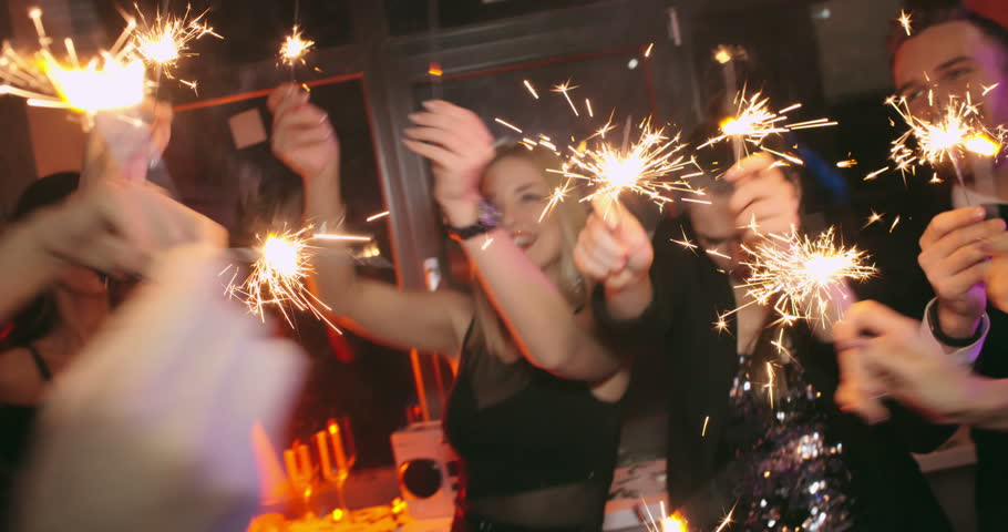 Handheld shot of carefree young men and women with glasses of champagne waving sparklers around, dancing and posing for camera in dark night club | Shutterstock HD Video #20624998
